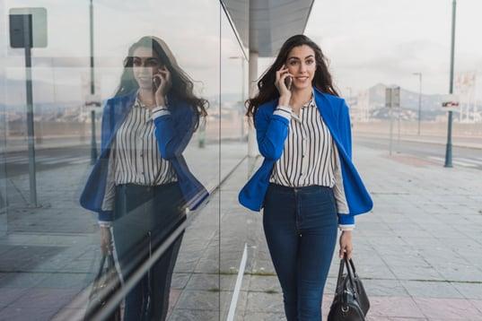 businesswoman-walking-while-talking-phone_23-2147604957